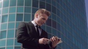 Porträt des angemessen-enthäuteten Geschäftsmannes, der draußen an einem sonnigen Sommertag steht und an Tablette arbeitet stock footage