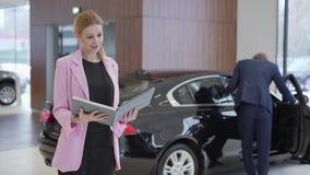 Porträt des angenehmen netten Mädchens in der rosa Jacke mit einem großen Buch über Autos vor den Paaren, die Fahrzeug wählen Man stock video