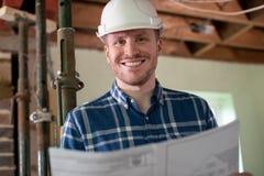 Porträt des Architekten Inside House Being erneuerte das Studieren von Plänen stockfoto