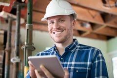 Porträt des Architekten Inside House Being erneuerte unter Verwendung Digital-Tablets stockbilder