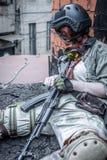 Porträt des Armeemädchens mit Gewehr in der Tarnung kleidet in der städtischen Szene, beim Verstecken Stockbild