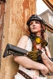 Porträt des Armeemädchens mit Gewehr in der Tarnung kleidet in der städtischen Szene, beim Verstecken Stockfotos