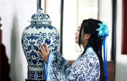 Porträt des asiatischen chinesischen Mädchens im Trachtenkleid, tragen blaue und weiße Porzellanart Hanfu und stehen am Tisch, de Lizenzfreies Stockbild
