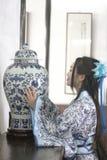 Porträt des asiatischen chinesischen Mädchens im Trachtenkleid, tragen blaue und weiße Porzellanart Hanfu und stehen am Tisch, de Stockbild