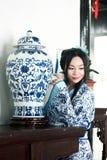 Porträt des asiatischen chinesischen Mädchens im Trachtenkleid, tragen blaue und weiße Porzellanart Hanfu und stehen am Tisch, de Stockfoto