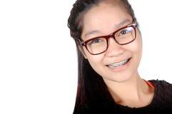 Porträt des asiatischen jungen Mädchens mit Gläsern und Klammern Stockfotos