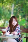 Porträt des asiatischen Mädchens 20 Jahre alt, Abnutzungskariertes hemd draußen aufwerfend Lizenzfreie Stockfotos