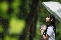 Porträt des asiatischen Schulmädchens, das mit Regenschirm am Naturgehweg auf dem Regnen geht lizenzfreie stockbilder