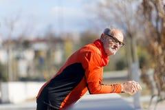 Porträt des athletischen älteren Mannes, der auf Zaun sich lehnt stockfotografie