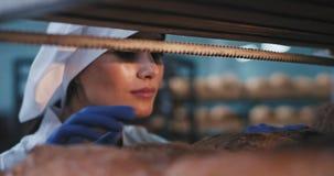 Porträt des attraktiven Bäckerfraueninneres der industriellen Regale vereinbart sie das frische gebackene Brot, sehr sorgfältig u stock video footage
