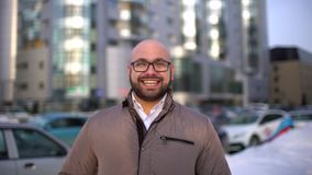 Porträt des attraktiven ernsten stilvollen jungen Mannes, der die Kamera untersucht und in der Stadt lächelt stock video