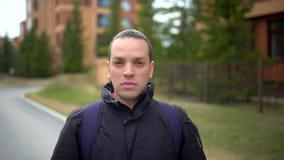 Porträt des attraktiven ernsten stilvollen jungen Mannes, der die Kamera untersucht und in der Stadt lächelt draußen stock video footage