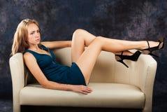 Porträt des attraktiven jungen Mädchens auf Sofa Lizenzfreie Stockfotografie