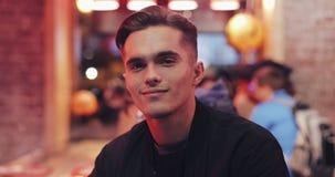 Porträt des attraktiven jungen Mannes am Nachtcafé lächelnd und die Kamera untersuchend Abendlichter im Hintergrund lizenzfreie stockfotos