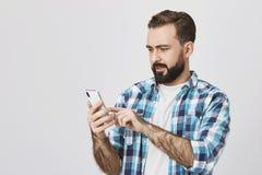 Porträt des attraktiven Kerls mit dem Bart und Schnurrbart, die Smartphone hält und des Grasennetzes mit überrascht und verdutzt lizenzfreies stockfoto