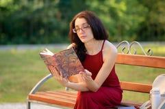 Porträt des attraktiven Mädchens in Eyesglasses und in rotem Kleid, die auf der Bank im Stadt-Park sitzen und irgendein Buch lese Stockfoto