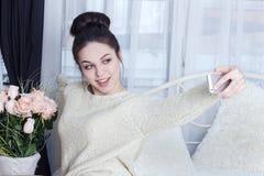 Porträt des attraktiven Mädchens selfie mit Blumen nehmend Lizenzfreies Stockbild