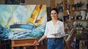 Porträt des attraktiven Malers der jungen Frau, der Kamera und lächelnde Stellung nahe ihrem schönen Bild in modernem betrachtet stock video footage