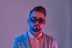 Porträt des attraktiven nachdenklichen Mannes in checkeret Blazer und sunglasse lizenzfreie stockfotos