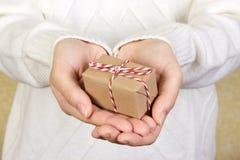 Porträt des attraktiven netten Mädchens im weißen Hemd des ärmellosen Sports, das Geschenkbox mit rotem Bogen über Segeltuchhinte lizenzfreie stockfotos