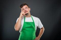 Porträt des attraktiven Supermarktarbeitgebers, der wie das Denken aufwirft Lizenzfreies Stockbild