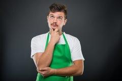Porträt des attraktiven Supermarktarbeitgebers, der wie das Denken aufwirft Stockbilder