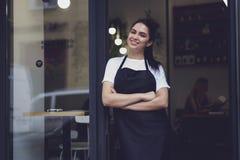 Porträt des attraktiven weiblichen barista, das in der Cafeteria arbeitet lizenzfreie stockbilder