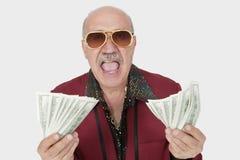 Porträt des aufgeregten älteren Mannes, der US-Banknoten mit Mund zeigt, öffnen sich gegen grauen Hintergrund Lizenzfreie Stockfotografie