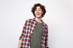 Porträt des aufgeregten lustigen lachenden jungen Mannes in der zufälligen Kleidung, welche die Kamera lokalisiert auf weißer Wan stockbilder
