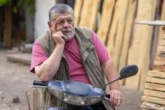 Porträt des bärtigen älteren Mannes, der auf einem Roller sitzt und in der Melancholie ist stockfotografie