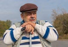 Porträt des bärtigen älteren Mannes mit Spazierstock Stockfotografie