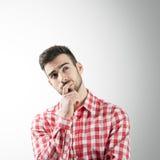 Porträt des bärtigen denkenden jungen Mannes, der oben schaut stockfotografie