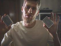 Porträt des bärtigen jungen Mannes, der Spielkarten hält, um Trick im dunklen Hintergrund zu machen lizenzfreie stockfotografie