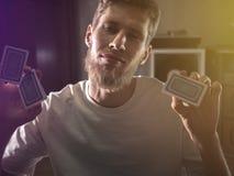 Porträt des bärtigen jungen Mannes, der Spielkarten hält, um Trick im dunklen Hintergrund zu machen stockbild
