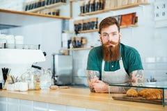 Porträt des bärtigen männlichen barista, das in der Kaffeestube steht Stockbild