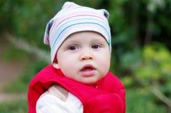 Porträt des Babys in der roten Weste draußen Stockbilder