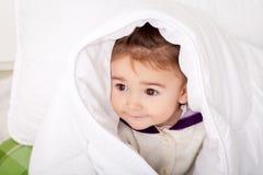 Porträt des Babys liegend im Bett unter featherbed Stockfoto