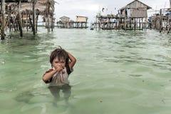 Porträt des Bajau-Stammjungen, der in der Mitte von Meer steht, die seine Weise zu seinem Haus verlor, Sabah Semporna, Malaysia stockbilder