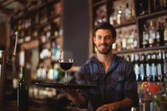 Porträt des Barangebots einen Behälter mit Glas Rotwein halten Lizenzfreies Stockfoto