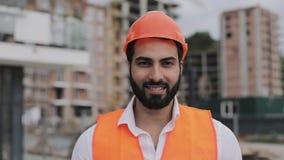 Porträt des Bauarbeiters auf Baustelle lächelnd an der Kamera Der Erbauer steht gegen den Hintergrund von a stock footage