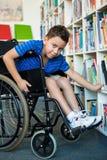 Porträt des behinderten Jungen Bücher in der Bibliothek suchend Lizenzfreie Stockbilder