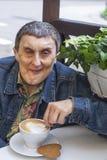 Porträt des behinderten Mannes mit der Zerebralparese, die am Café und an trinkendem Kaffee sitzt Stockfotografie