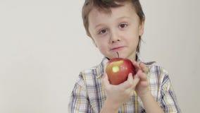 Porträt des beißenden Apfels des kleinen Jungen stock footage