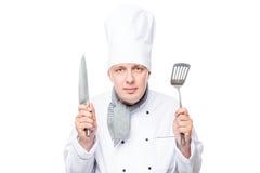 Porträt des bereiten Chefs mit Schaufel und einem scharfen Messer auf einem Weiß Lizenzfreies Stockfoto