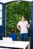 Porträt des bereitstehenden Balkons der glücklichen jungen Geschäftsfrau mit Laptop auf Schreibtisch Stockfoto