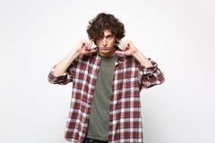 Porträt des beteiligten jungen Mannes in der zufälligen Kleidung, welche die Kamera bedeckt Ohren mit den Fingern lokalisiert auf lizenzfreies stockbild