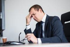 Porträt des betonten Geschäftsmannes, der im modernen Büro sitzt lizenzfreie stockfotografie