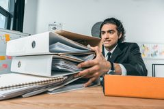 Porträt des betonten Geschäftsmannes, der Ordner mit Dokumenten hält Stockfotografie