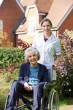 Porträt des Betreuers ältere Frau im Rollstuhl drückend stockfotografie