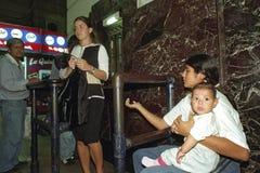 Porträt des Bittens der Mutter mit Baby auf Bahnstation Lizenzfreie Stockfotos
